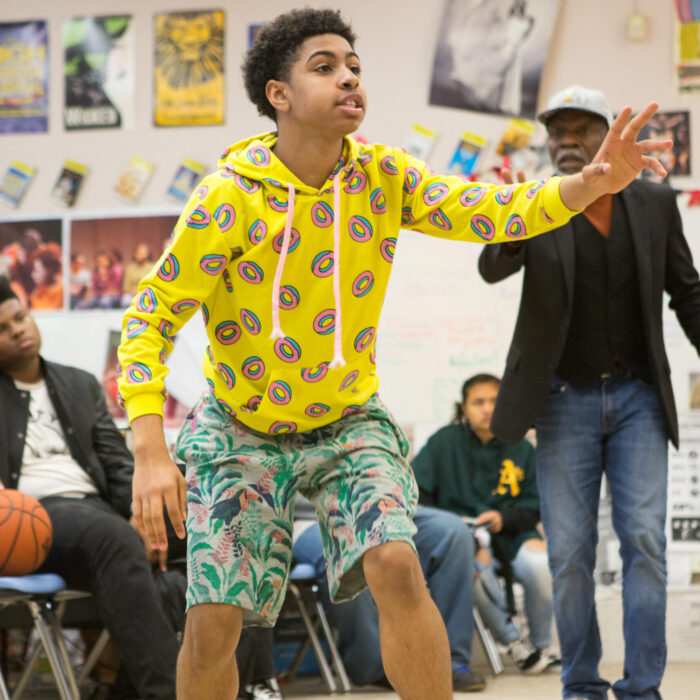 A high school drama student rehearses a scene while his instructor looks on.