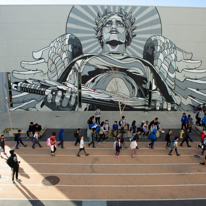 Students at UCLA Community School pass by one of several outdoor campus murals on their way to class.